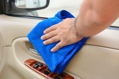Entregue o painel interior de limpeza da porta de carro com pano do microfiber Foto de Stock Royalty Free