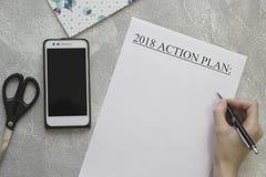 Entregue o plano de ação 2018, telefone celular, tesouras da escrita Fotos de Stock