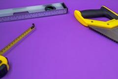 Entregue o ruller das ferramentas, grampeador, da mão fita métrica da serra do amarelo fotografia de stock royalty free