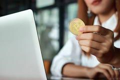Entregue o ` s da mulher de negócio que guarda a moeda dourada do bitcoin do cryptocurrency Dinheiro virtual em digital Imagens de Stock