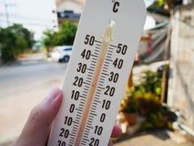 Entregue o termômetro da posse que mostra a temperatura nos graus Célsio Imagem de Stock