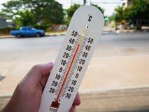 Entregue o termômetro da posse que mostra a temperatura nos graus Célsio Fotos de Stock