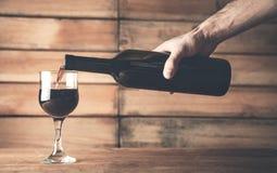 Entregue o vinho tinto de derramamento em um vidro em um fundo de madeira imagens de stock royalty free