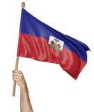 Entregue orgulhosamente a ondulação da bandeira nacional de Haiti Foto de Stock