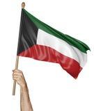 Entregue orgulhosamente a ondulação da bandeira nacional de Kuwait Fotografia de Stock Royalty Free