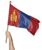 Entregue orgulhosamente a ondulação da bandeira nacional de Mongólia Imagem de Stock
