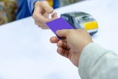 Entregue pagar o cartão de crédito no terminal do pagamento com caixa imagem de stock