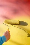 Entregue a parede amarela de pintura pela escova do pintor do rolo foto de stock