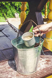 Entregue pegarar a água da caneca do ferro da cubeta Fotos de Stock