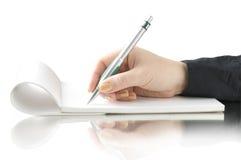 Entregue a pena e a escrita do sustento no caderno imagem de stock royalty free
