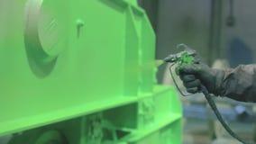 Entregue a pintura de uma superfície de metal pela arma de pulverizador filme