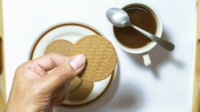 Entregue a posse biscoitos marrons no prato que emparelha-se com o café preto com Imagens de Stock Royalty Free