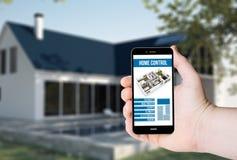 Entregue a posse um telefone com sistema de controlo home remoto em uma tela fotos de stock royalty free