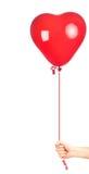 Entregue prender um balão vermelho dado forma coração fotos de stock royalty free