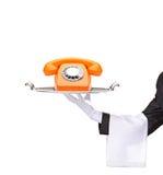 Entregue prender uma bandeja com um telefone alaranjado Imagem de Stock
