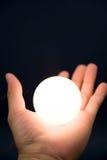 Entregue prender uma esfera brilhante imagem de stock