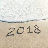 Entregue a rotulação do subtítulo do ano novo feliz 2018 na areia da praia com fotos de stock royalty free