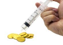 entregue a seringa da injeção e a pilha de moedas no dinheiro c do custo do orçamento fotos de stock