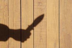 Entregue a silhueta com a faca no painel de madeira natural Fotografia de Stock Royalty Free