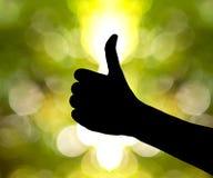 Entregue a silhueta sob um fundo do bokeh, o símbolo de wi de uma mão Imagem de Stock Royalty Free