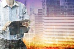 Entregue a tabuleta da posse com skyline abstrata Backgr do negócio e da cidade Imagem de Stock