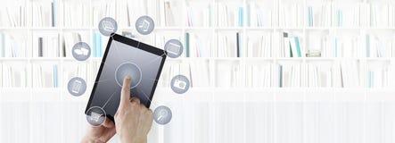 Entregue tabuleta digital tocante com os ícones isolados na parte traseira da biblioteca imagem de stock