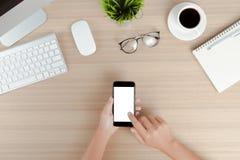 Entregue a telefone do uso a tela branca móvel na opinião de tampo da mesa do trabalho Foto de Stock Royalty Free