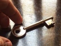 entregue a tomada de uma chave no conceito da tabela Imagens de Stock Royalty Free