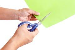 Entregue usando as tesouras que cuting o papel verde, isolado no branco Fotografia de Stock