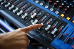 Entregue usando o console de mistura, sagacidade de mistura da mesa do estúdio de gravação sonora fotografia de stock