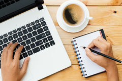 Entregue usando o portátil e escreva a nota inspiram a ideia na madeira Imagens de Stock Royalty Free