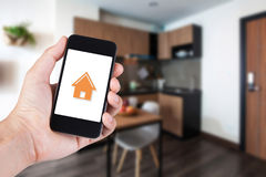 Entregue usando o smartphone pela casa esperta do app no móbil imagens de stock royalty free