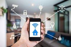 Entregue usando o smartphone pela casa esperta do app no móbil fotografia de stock