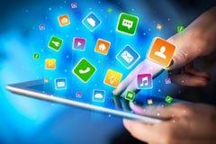 Entregue usando a tabuleta com os ícones da aplicação que voam ao redor Foto de Stock Royalty Free