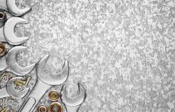 Entreißen Sie Werkzeuge und Nüsse auf einem metallischen Hintergrund Lizenzfreies Stockfoto