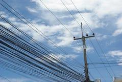 Entrelazamiento de muchos alambres eléctricos en polos Fotografía de archivo