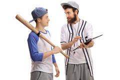 Entrenador de béisbol que aconseja a un jugador de béisbol adolescente imagen de archivo libre de regalías