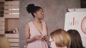Entrenador femenino afroamericano acertado del negocio que entrena al equipo multiétnico en la cámara lenta corporativa del semin almacen de video