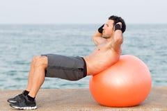 Entrenamiento abdominal de la bola en el lado de mar foto de archivo libre de regalías
