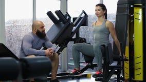 Entrenamiento activo de la mujer joven en el gimnasio, hablando con el hombre juguetón hermoso, arriba cinco metrajes