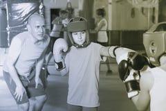 Entrenamiento adolescente de la muchacha positiva en el entrenamiento del boxeo con el coche Foto de archivo