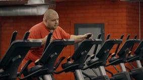 Entrenamiento agotado pesado de la mirada gorda y hombre grande en club de fitness almacen de metraje de vídeo