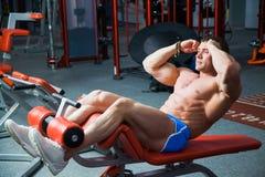 Entrenamiento apto de los músculos abdominales del tren del torso de la elevación del hombre en el gimnasio Fotos de archivo
