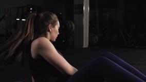 Entrenamiento apto deportivo de la muchacha con la placa del peso en gimnasio Mujer joven que hace sentar-UPS con el peso en el p metrajes