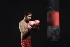 Entrenamiento asiático joven del boxeo del hombre con el saco de arena Foto de archivo