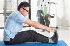 Entrenamiento asiático maduro del hombre en el gimnasio Fotografía de archivo