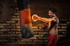 Entrenamiento asiático potente del hombre del boxeador con el saco de arena Imagenes de archivo
