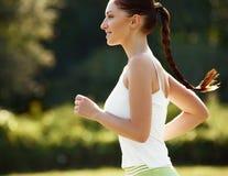 Entrenamiento atlético del corredor en un parque para el maratón. Muchacha Ru de la aptitud Imagenes de archivo