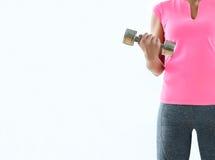 Entrenamiento atractivo anónimo con pesas de gimnasia, fondo blanco de la mujer Foto de archivo libre de regalías