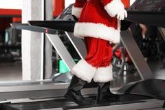 Entrenamiento auténtico de Santa Claus en la rueda de ardilla en gimnasio moderno imagen de archivo libre de regalías